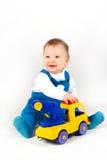 Niño pequeño feliz que juega con los coches y los juguetes. Fotos de archivo