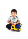 Niño pequeño feliz que juega con los coches y los juguetes. Fotografía de archivo
