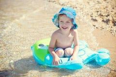 Niño pequeño feliz que juega el círculo de goma Foto de archivo