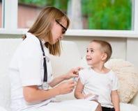 Niño pequeño feliz que recibe la inyección o la vacuna foto de archivo