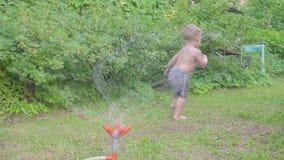 Niño pequeño feliz que se divierte afuera con la regadera del agua en jardín del verano Cámara lenta almacen de metraje de vídeo