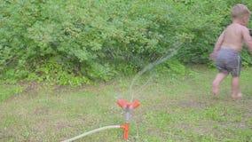 Niño pequeño feliz que se divierte afuera con la regadera del agua en jardín del verano Cámara lenta metrajes
