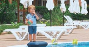 Niño pequeño feliz que se sienta cerca de la piscina metrajes