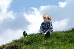 Niño pequeño feliz que se sienta en hierba verde fotos de archivo
