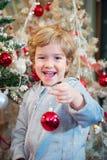Niño pequeño feliz que sostiene la bola de la Navidad y que la adorna Fotos de archivo