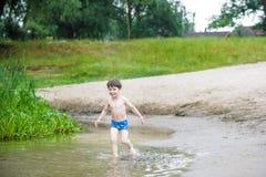 Niño pequeño feliz que tiene la diversión y funcionamiento en agua en el río en el tiempo del día de verano, forma de vida al air Fotografía de archivo