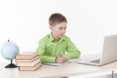 Niño pequeño feliz que usa el ordenador portátil en la tabla fotografía de archivo