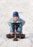 Niño pequeño feliz sledging en el sleig Fotografía de archivo libre de regalías