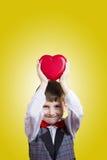 Niño pequeño feliz, sonriente que lleva a cabo el corazón rojo fotos de archivo