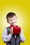 Niño pequeño feliz, sonriente que lleva a cabo el corazón rojo i fotografía de archivo
