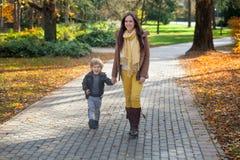 Niño pequeño feliz y su madre que caminan en parque Imagen de archivo libre de regalías