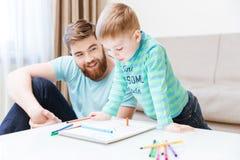 Niño pequeño feliz y su padre que unen Imagen de archivo libre de regalías