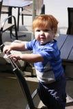 Niño pequeño formado del jengibre con los ojos azules que permanecen en el wicke Imagen de archivo libre de regalías