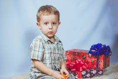 Niño pequeño fotografiado en la Navidad del estudio con los regalos Foto de archivo libre de regalías