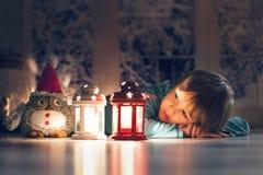 Niño pequeño hermoso, acostándose en el piso, mirando la vela Imagenes de archivo