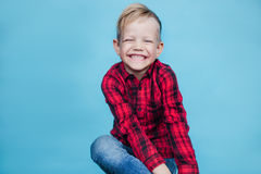 Niño pequeño hermoso con la camisa roja Moda Retrato del estudio sobre fondo azul Imágenes de archivo libres de regalías