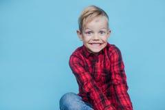Niño pequeño hermoso con la camisa roja Moda Retrato del estudio sobre fondo azul Imagenes de archivo