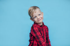 Niño pequeño hermoso con la camisa roja Moda Retrato del estudio sobre fondo azul Foto de archivo libre de regalías