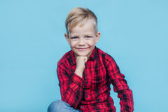 Niño pequeño hermoso con la camisa roja Moda Retrato del estudio sobre fondo azul Fotos de archivo