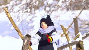 Niño pequeño hermoso en parque del invierno Él se sienta en una cerca de madera y juegos con un palillo metrajes