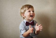 Niño pequeño hermoso que ríe y que aplaude fotos de archivo