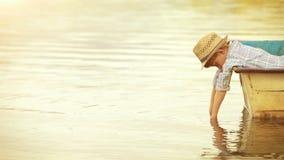 Niño pequeño hermoso que se enfría hacia fuera en el barco en el río almacen de metraje de vídeo