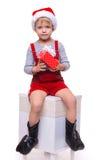 Niño pequeño hermoso que se sostiene presente de Santa Claus Navidad Foto de archivo