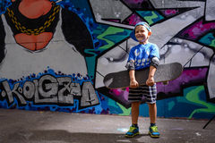 Niño pequeño hermoso que sostiene su monopatín Fotografía de archivo libre de regalías