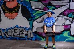 Niño pequeño hermoso que sostiene su monopatín Foto de archivo libre de regalías