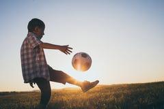 Niño pequeño joven que juega en el campo con el balón de fútbol Imágenes de archivo libres de regalías