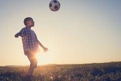 Niño pequeño joven que juega en el campo con el balón de fútbol Fotos de archivo libres de regalías