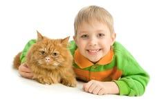 Niño pequeño juguetón y gato rojo serio Imagen de archivo
