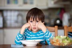 Niño pequeño lindo, comiendo los espaguetis en casa para la hora de comer Imágenes de archivo libres de regalías