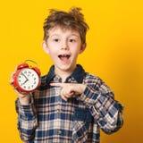 Niño pequeño lindo con el despertador, aislado en amarillo Niño divertido que señala en el despertador a las 7 en la mañana Exced foto de archivo