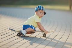 Niño pequeño lindo con el monopatín al aire libre Imagen de archivo