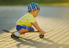 Niño pequeño lindo con el monopatín al aire libre Imagen de archivo libre de regalías