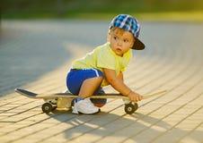 Niño pequeño lindo con el monopatín al aire libre Imagenes de archivo