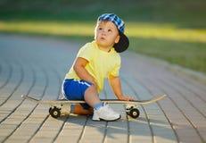 Niño pequeño lindo con el monopatín al aire libre Fotos de archivo