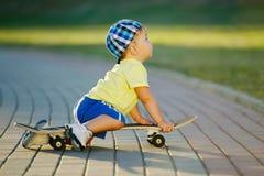Niño pequeño lindo con el monopatín al aire libre Fotografía de archivo libre de regalías