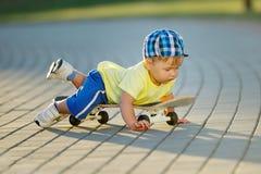 Niño pequeño lindo con el monopatín al aire libre Foto de archivo