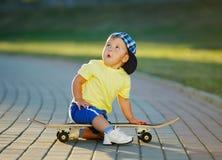 Niño pequeño lindo con el monopatín al aire libre Foto de archivo libre de regalías
