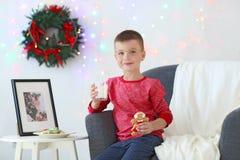 Niño pequeño lindo con el vidrio de la leche y de la galleta en el sitio adornado para la Navidad Fotos de archivo