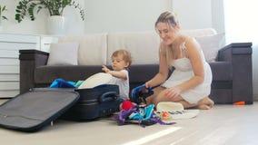 Niño pequeño lindo con la maleta del embalaje de la madre para las vacaciones en piso en la sala de estar almacen de video