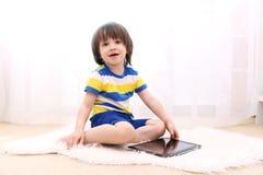 Niño pequeño lindo con la tableta en casa Fotos de archivo libres de regalías