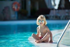Niño pequeño lindo con las gafas de sol por la piscina Imagen de archivo