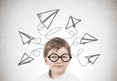 Niño pequeño lindo con los vidrios, aviones de papel Foto de archivo libre de regalías