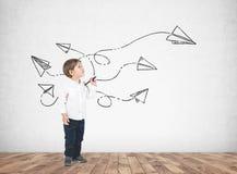 Niño pequeño lindo con un marcador, aviones de papel Foto de archivo libre de regalías