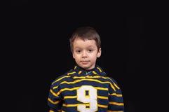 Niño pequeño lindo con una mirada seria Foto de archivo libre de regalías