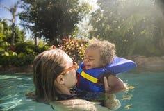 Niño pequeño lindo de la raza mixta que juega con su madre en un tropical fotografía de archivo