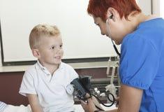Niño pequeño lindo del doctor Examining imagenes de archivo